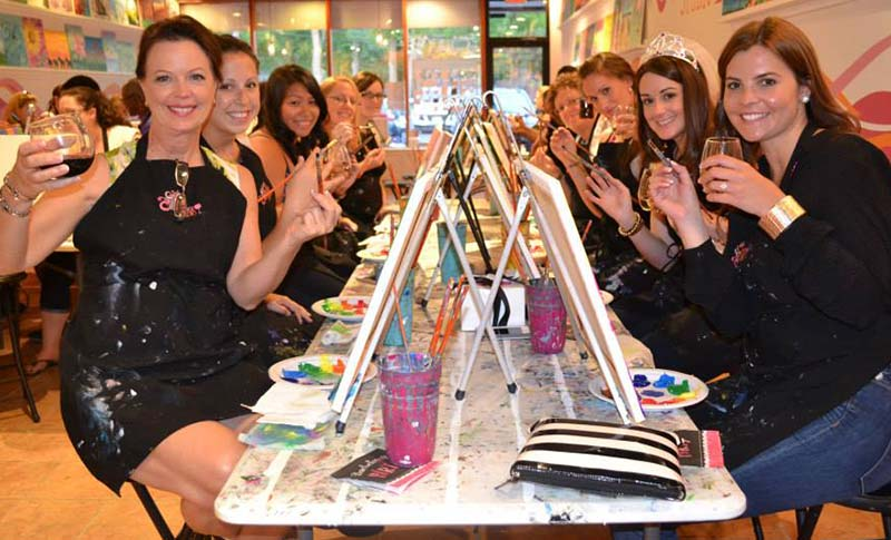 a group of women holding wine glasses & paint brushes at a paint & sip bachelorette party